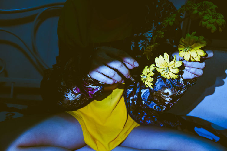 Midsection of woman holding yellow flowers while sitting on bed