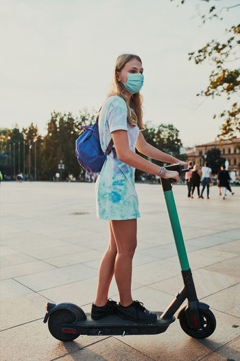 Full length of girl wearing mask standing on electric push scooter on street