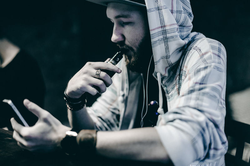 Vaping Bad Habit Cellphone Close-up Communication Day Holding Lifestyles Men Mobile Phone One Person Outdoors Portable Information Device Real People Sitting Smart Phone Technology Using Phone Vape Wireless Technology Young Adult Young Men