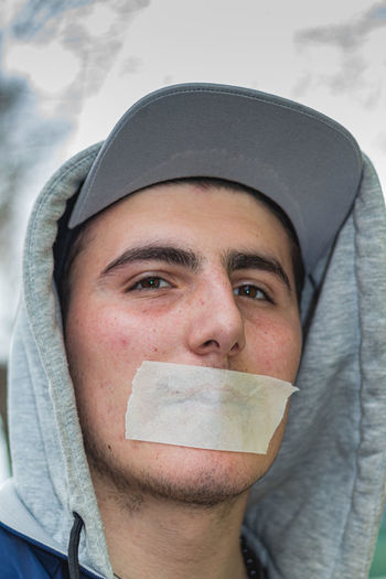 Close-up portrait of young man with adhesive tape on mouth