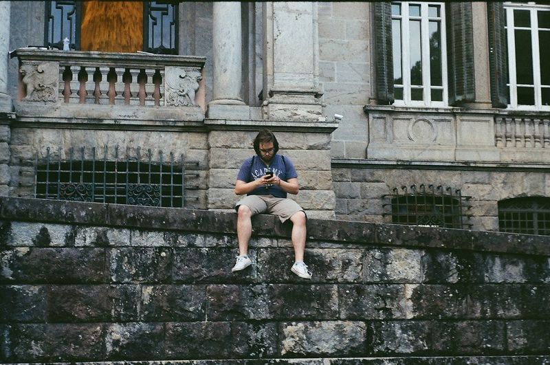 Full length of man sitting on staircase against building