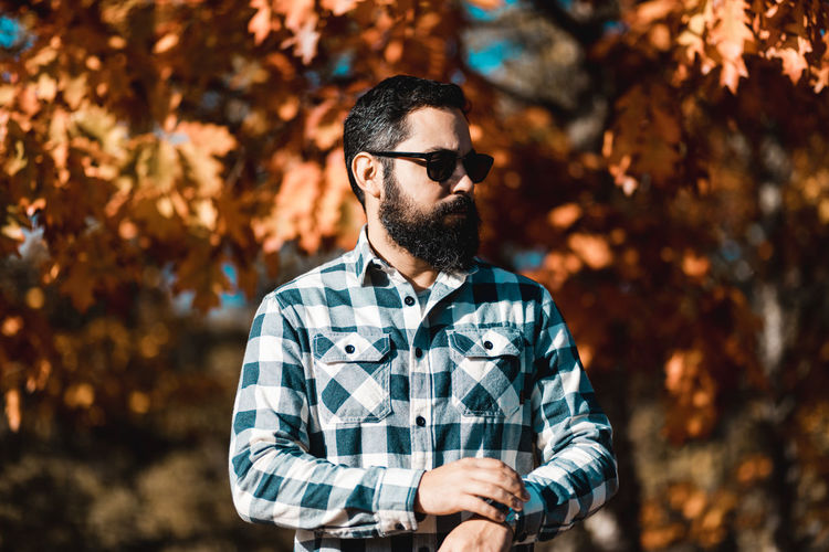 Man wearing sunglasses while standing against trees