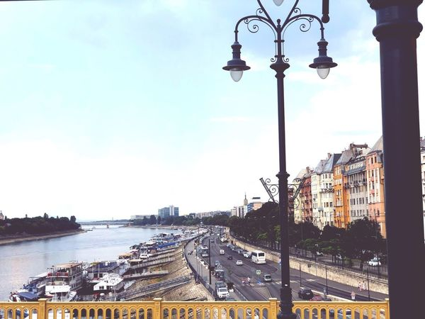 A. View looking down The River Danube in Budapest. Traffic Road Danube River Budapest Street Light Sky Lighting Equipment Architecture Street Built Structure Building Exterior City Day Transportation Travel Outdoors Water