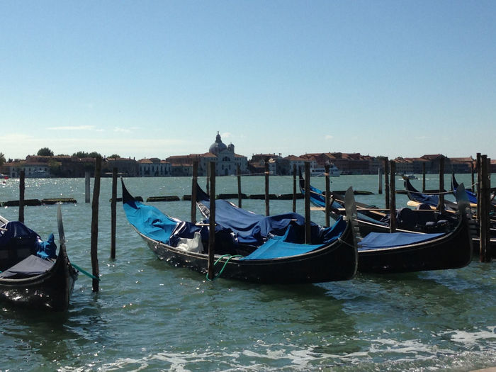 Gondolas moored in grand canal against sky