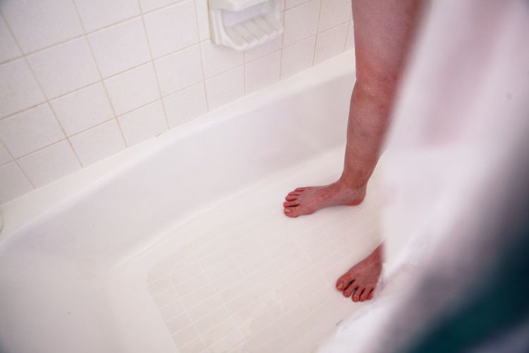 Low Section Of Person Standing In Bathtub