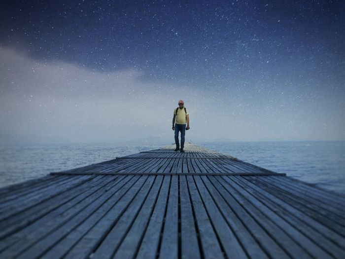 Man standing on pier over against sky at night
