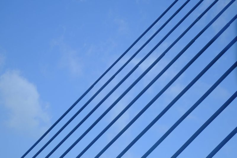 Low angle view of cables against blue sky