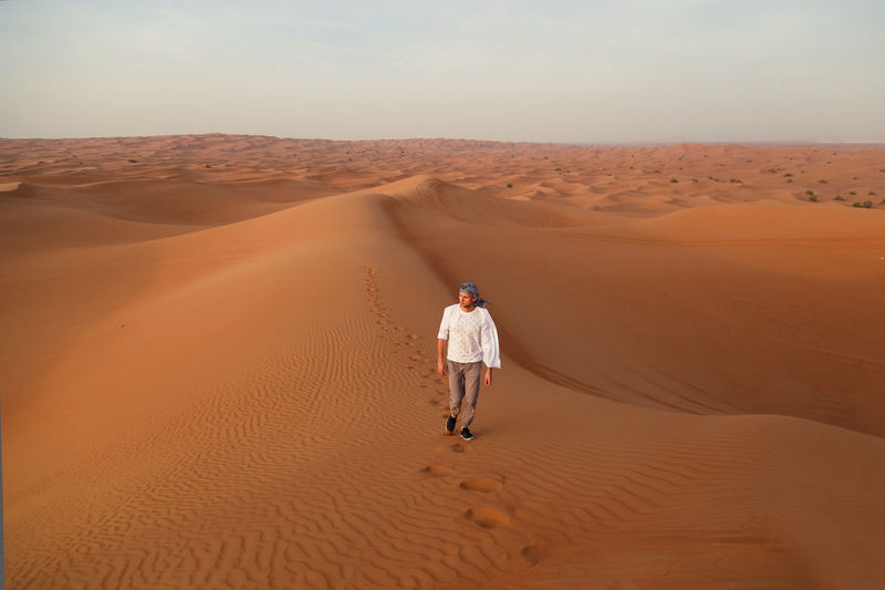High angle view of man on sand dune in desert against sky