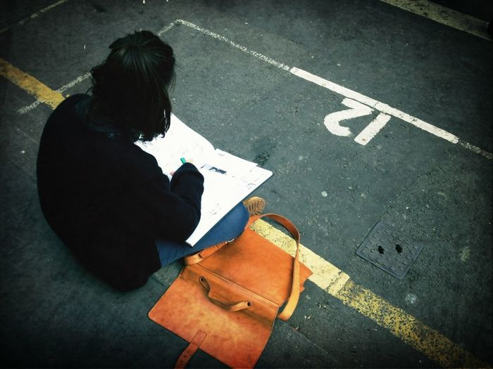 High angle view of woman sitting on street and drawing