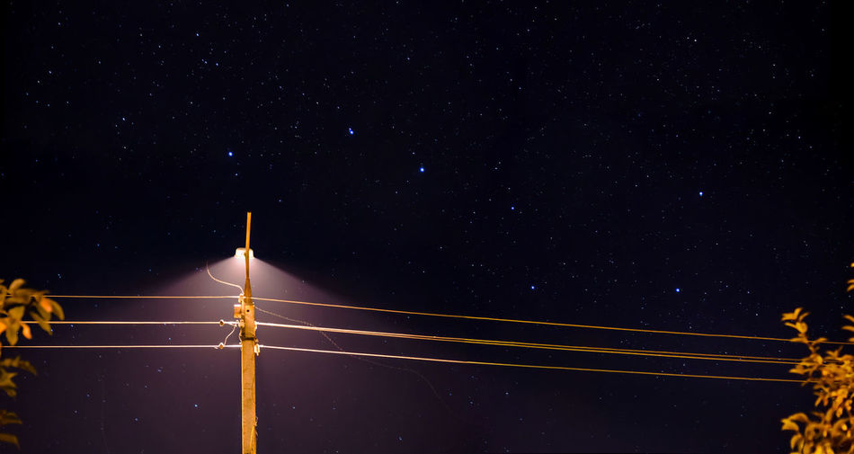 Low Angle View Of Illuminated Street Light Against Star Field