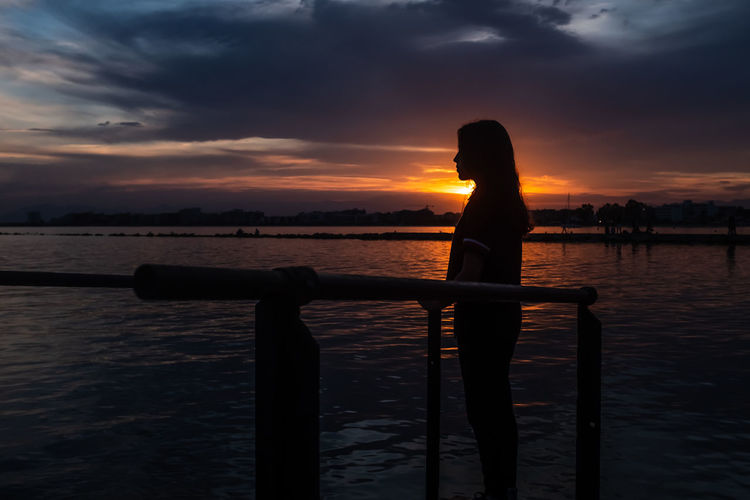Young teenage girl with long hair at sunset beach looking in the distance. concept of introspection.