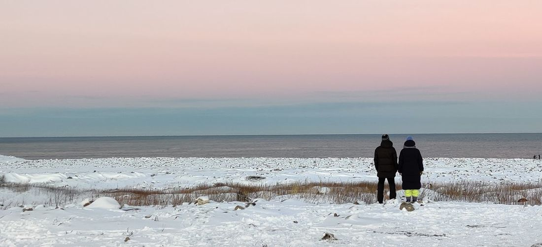 Rear view of men on beach against sky during sunset