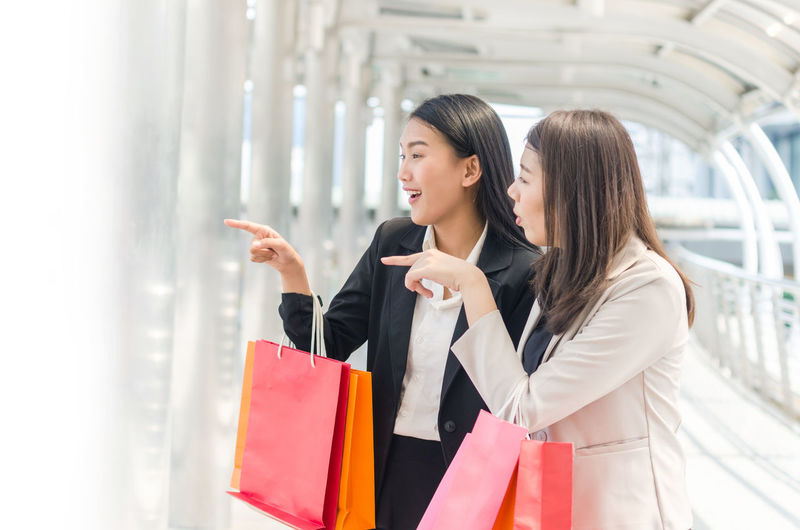 Cheerful young women looking away while holding shopping bags