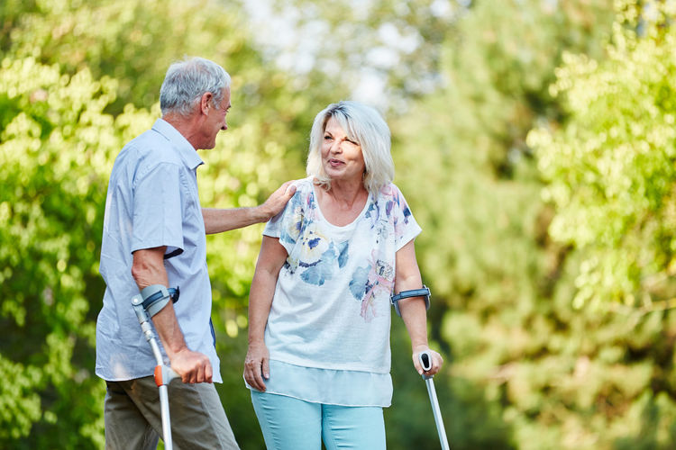 Senior couple with walking canes standing against trees at park