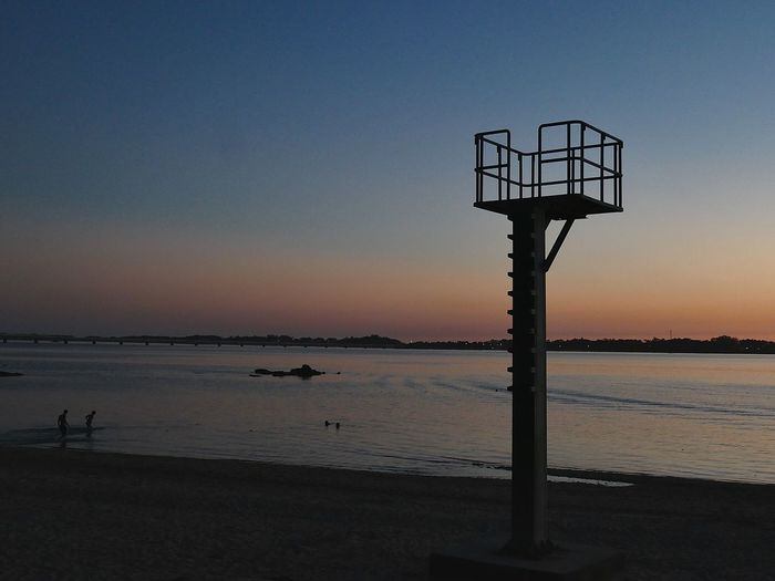 Silhouette lifeguard hut on beach against clear sky during sunset