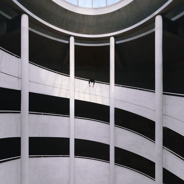 Low angle view of man hanging in balcony of building