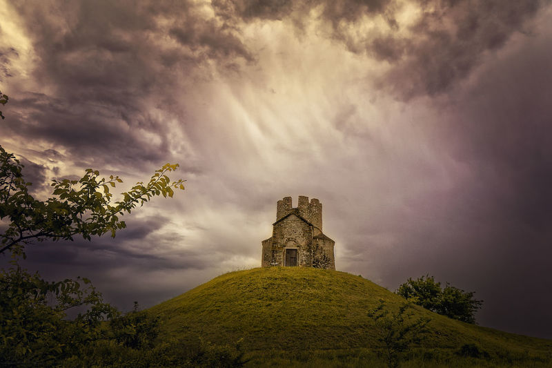 Low angle view of castle on hill against cloudy sky