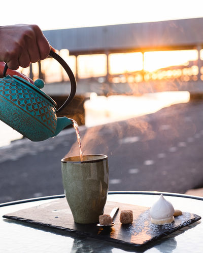 Hand Human Hand Human Body Part Real People Cup Close-up Focus On Foreground Food And Drink Holding Nature Day Container One Person Sunlight Table Pouring Outdoors Mug Kitchen Utensil Tea Cup Finger