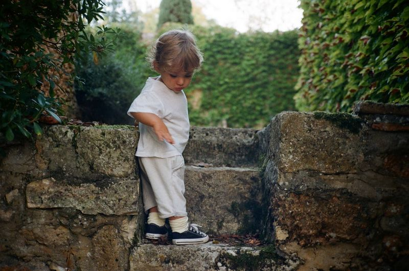 Rear view of boy looking at stone wall
