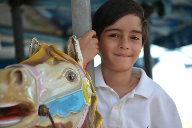Portrait of smiling boy on carousel horses