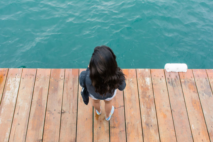 High Angle View Of Woman Standing On Pier In Sea