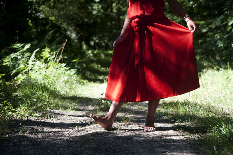 Low Section Of Woman In Red Dress Standing Against Trees