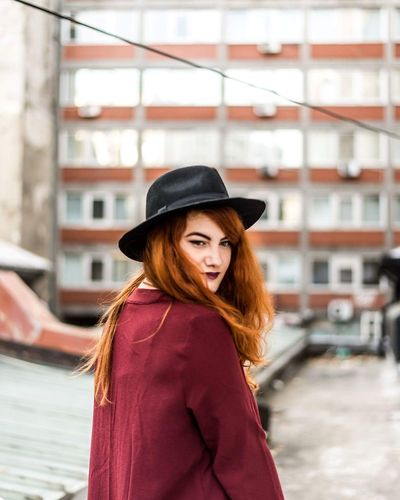 Beautiful redhead woman wearing hat against building in city