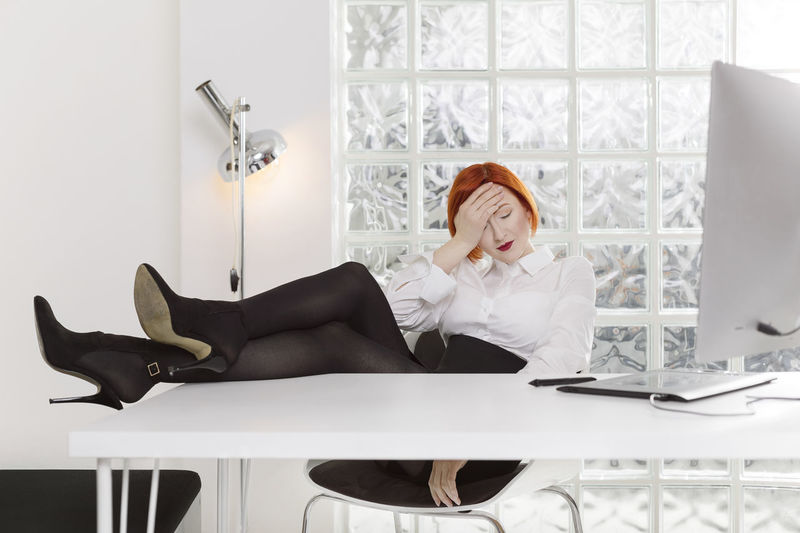 Full Length Of Businesswoman With Headache Resting Legs On Desk