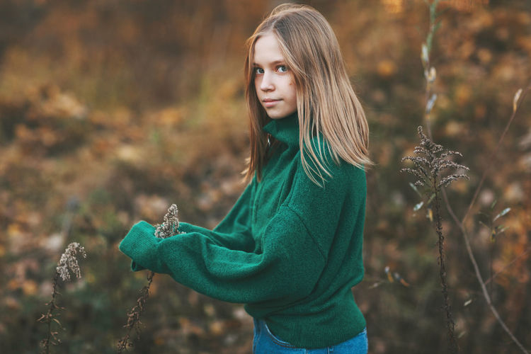 Portrait of a beautiful teenage girl with blond hair and blue eyes in an autumn park