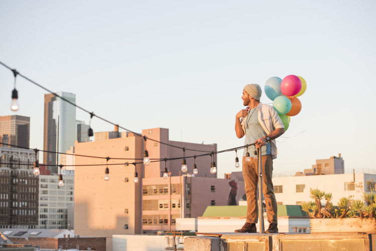 Low angle view of balloons against buildings in city