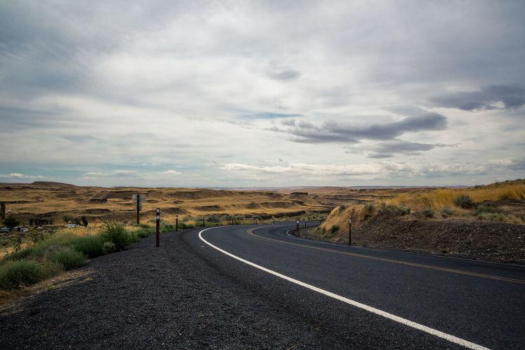 Road leading towards landscape against sky