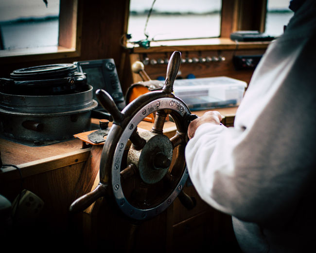 Midsection Of Man Driving Nautical Vessel