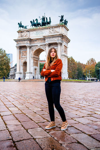Portrait of beautiful young woman against monument