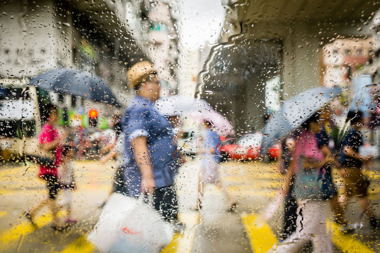 People Walking On Street Seen Through Wet Windshield