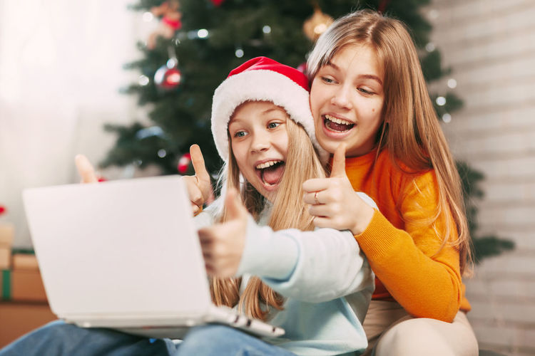 Young woman using mobile phone while sitting on christmas tree