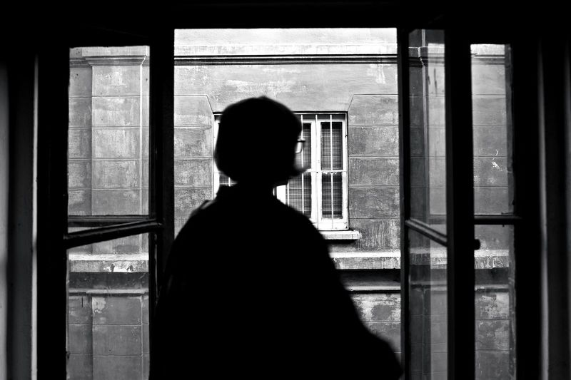 Rear view of silhouette woman looking through window