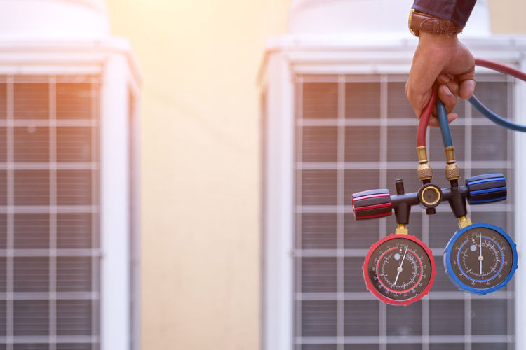 Cropped hand of person holding pressure gauge