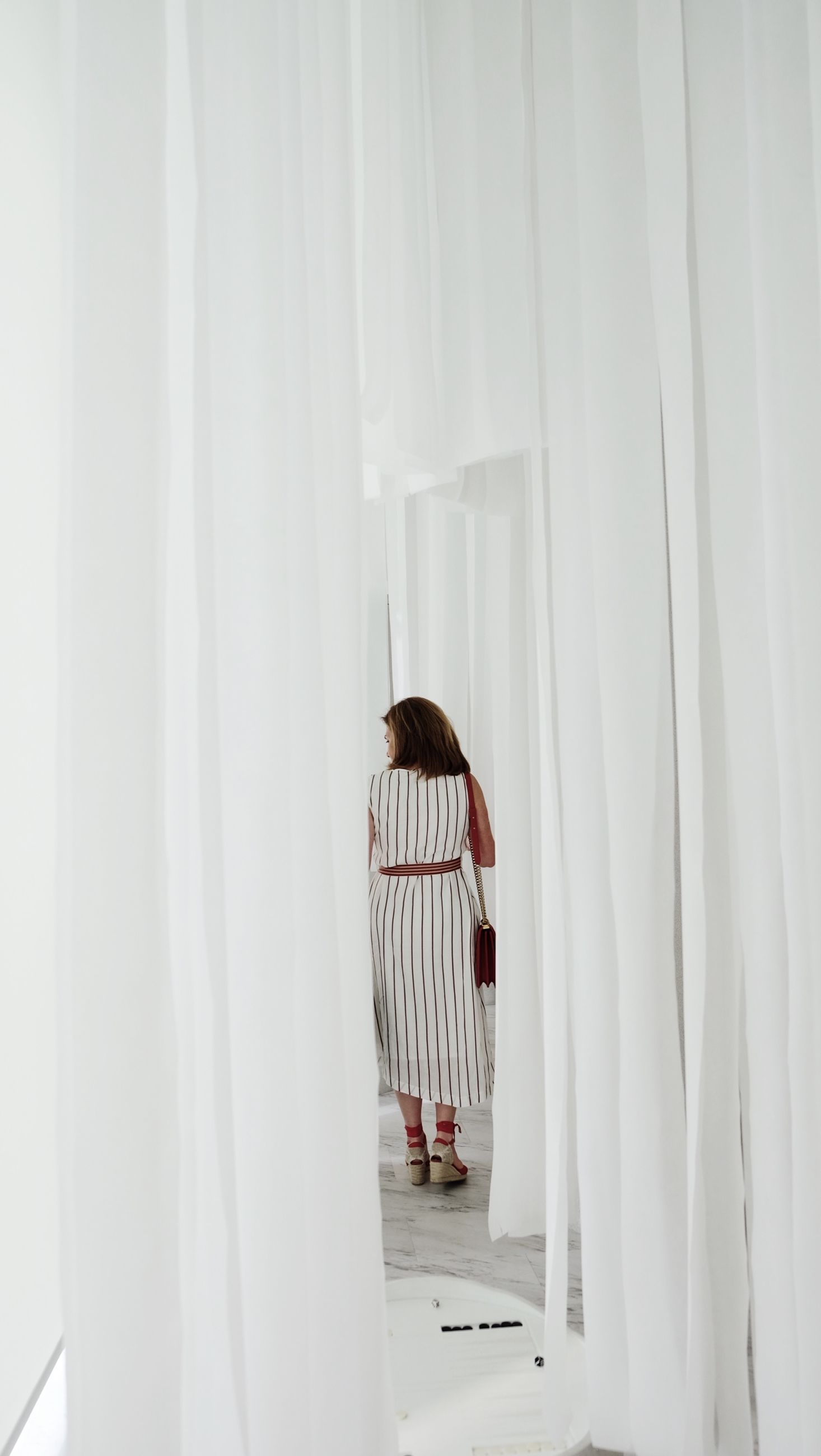 curtain, indoors, white color, one person, real people, textile, home interior, standing, lifestyles, architecture, white, window, hanging, women, seat, adult, day, young adult