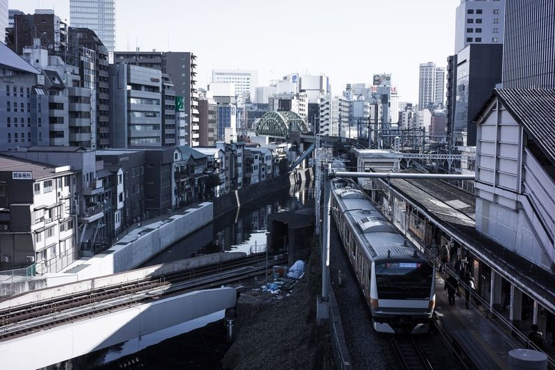 High angle view of train on railroad tracks amidst buildings in city