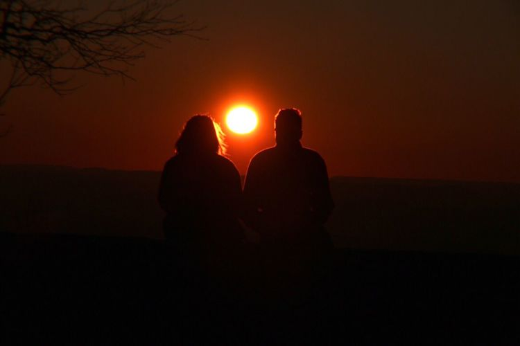Silhouette Of Couple Sitting Against Sky At Sunset