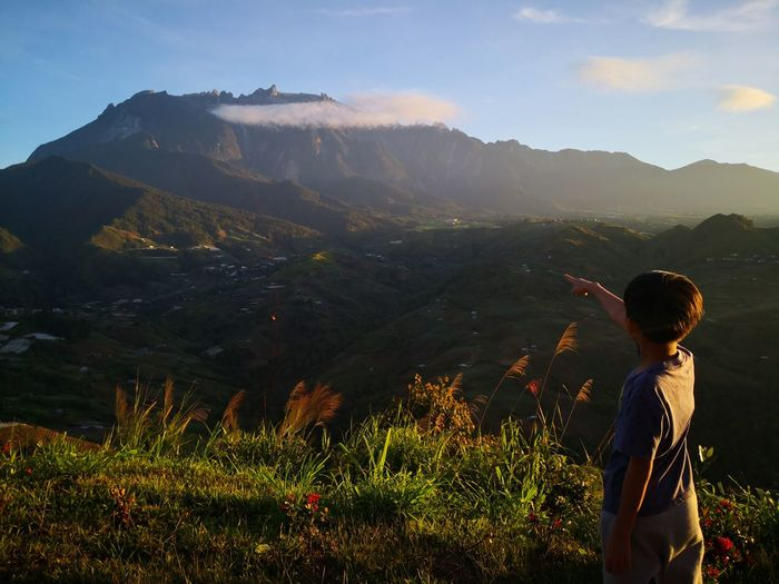 Boy looking at mountains against sky