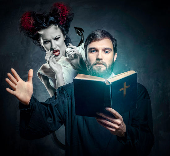 Digital Composite Image Of Scared Female Demon Hiding Behind Priest Reading Bible