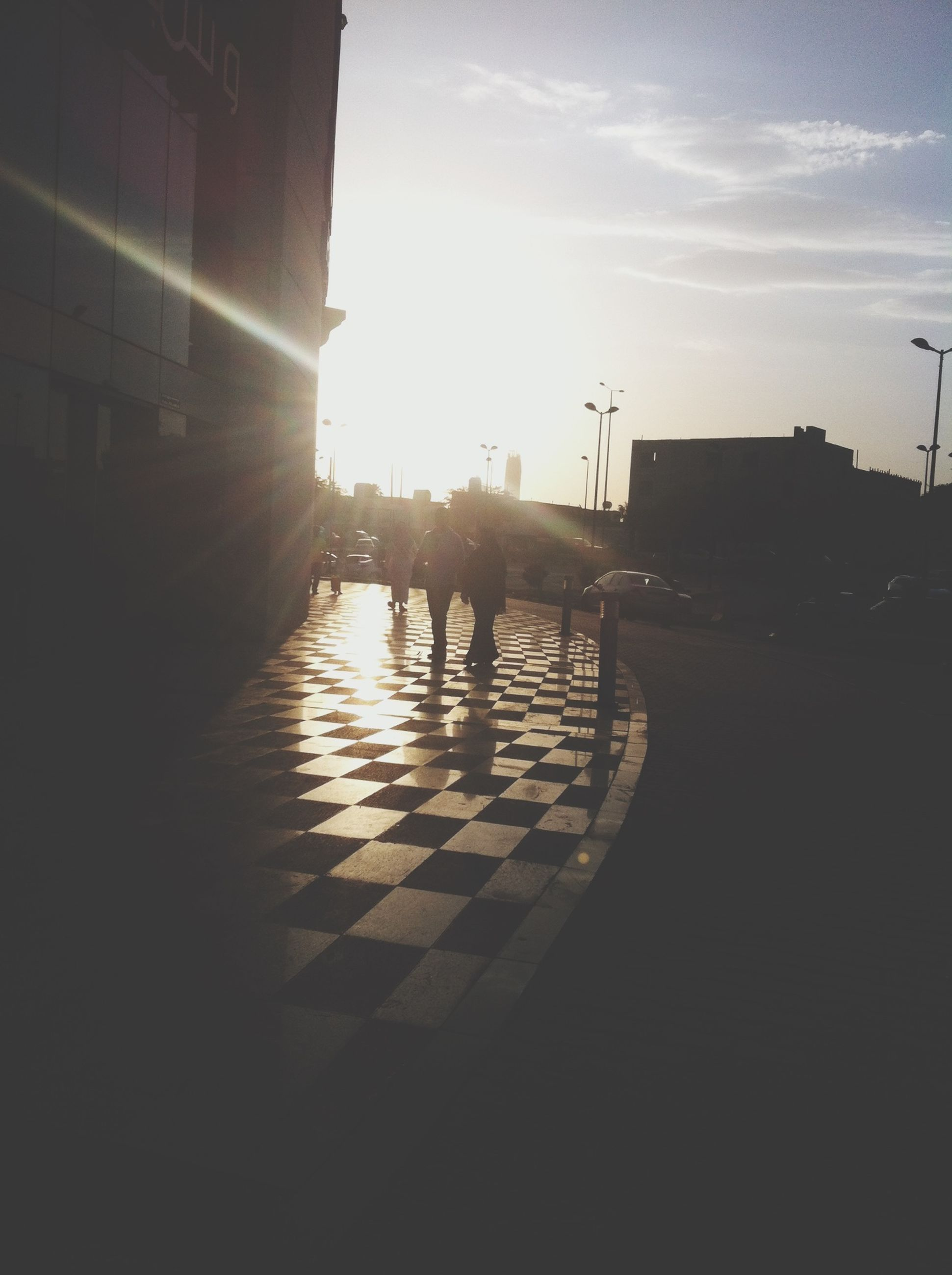sun, sunlight, sunbeam, built structure, architecture, building exterior, lens flare, sunset, sky, lifestyles, silhouette, men, leisure activity, walking, street, sunny, city, outdoors