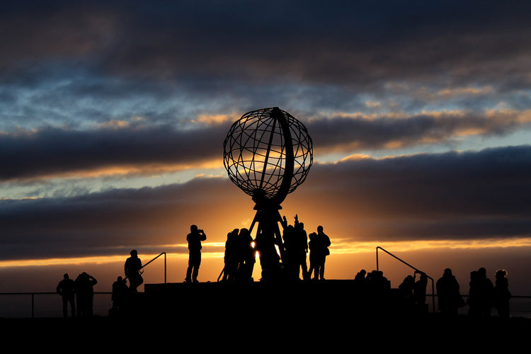 Silhouette people at metallic globe against sky during sunset