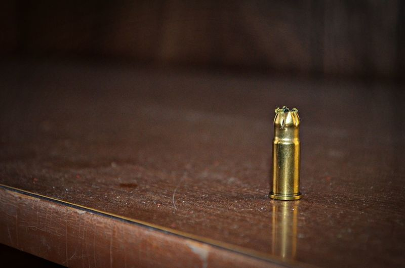 Close-up Of Gold Bullet Casing On Table