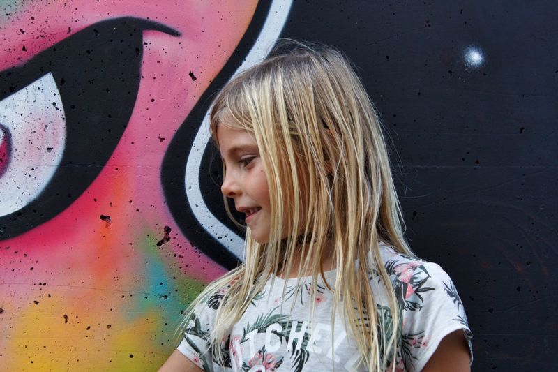 Smiling girl looking away against painted wall