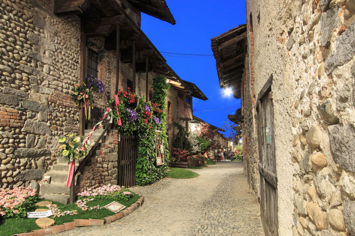 Candelo, Biella - May 4, 2016: View form the inside of the Medieval village of Ricetto di Candelo in Piedmont, used as a refuge in times of attack during the Middle Age. Alley Architecture Biella Blue Building Building Exterior Built Structure Candelo Candelo In Fiore Day Growth Italy Medieval Village Narrow No People Outdoors Plant Residential Building Residential Structure Ricetto Di Candelo  Sky Sunlight Sunny The Way Forward Town