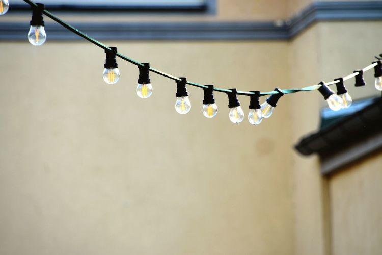 Low angle view of illuminated light bulbs hanging