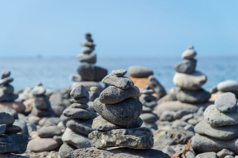 Stack of stones on rocky shore at sea