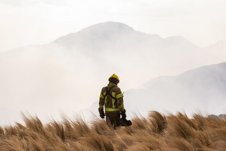 Rear view of man on field against mountain range